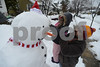 02.13.14 BALTIMORE, MD- Northeast Baltimore resident Earl Millett holds his neighbors 4 year old daughter, Paige Hutchenson, up to put the finishing touches to a snowman that was a team effort on his street. More than a foot of snow fell on most of Maryland as a nor'easter passed over the east coast overnight, starting around 8pm on Wednesday February 12, 2014. (The Daily Record/Maximilian Franz)