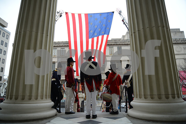 3-25-14  BALTIMORE, MD- Reenactors from the Fort McHenry National Monument and Historic shrine stand on the steps looking out a huge American Flag at the Baltimore Basilica during the Maryland Day ceremony honoring the legacy of Cecilius Calvert, 2nd Lord Baltimore and founder of Maryland in 1634. (The Daily Record/Maximilian Franz)